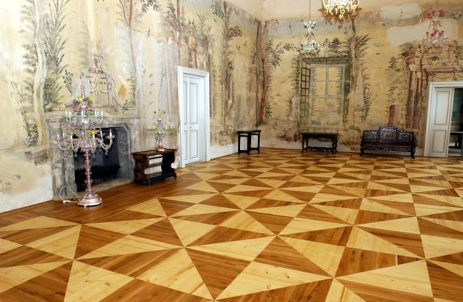 Kazetová podlaha složená pouze ze dvou barev dřeva vypadá v prostoru velmi elegantně.