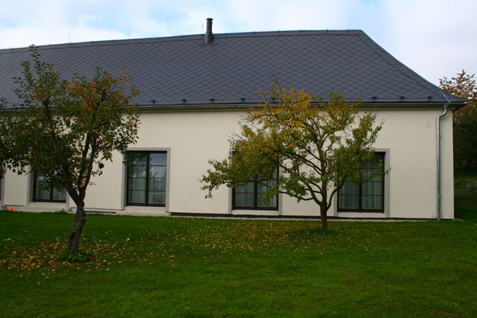 Francouzská okna z lepených profilů jsou umístěna přes celou jednu stěnu a umožňují tak krásný výhled z hlavní obytné části domu.