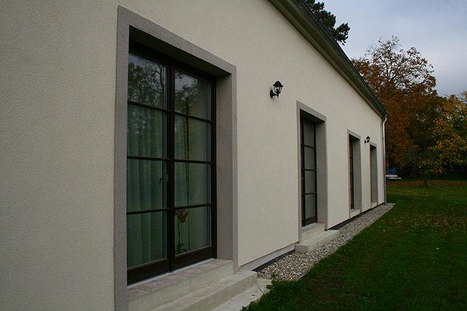 Dřevěná okna na míru propojují hlavní obytný prostor se zahradou.