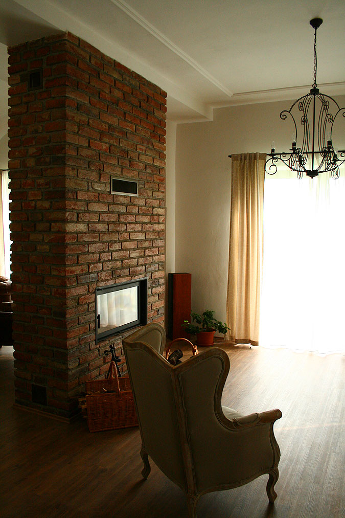 Pohled z druhé strany krbu, jehož příjemné působení je možné si takto vychutnat z více zákoutí domu.