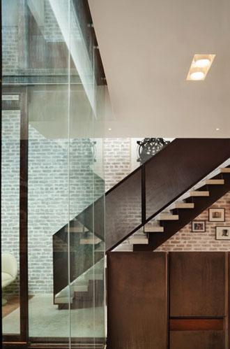 V bytě se opakuje často motiv velkých ploch cihelného zdiva, oceli a skla.