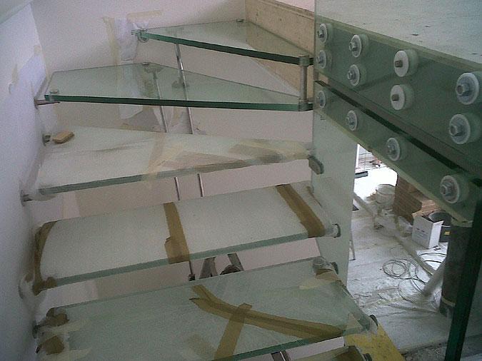 Dokončovací práce na celoskleněném schodišti. Každý stupeň po dobu stavby chrání folie.