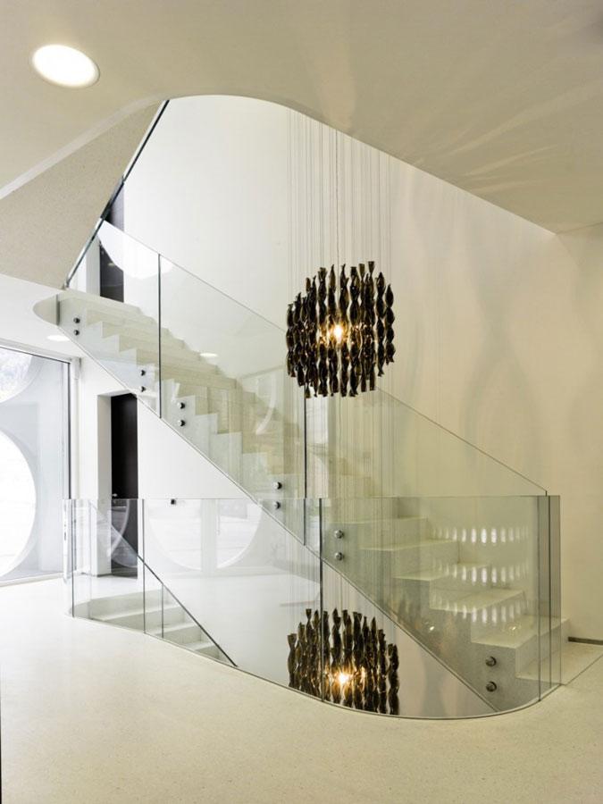 Monolitické betonové schodiště se skleněným zábradlím.