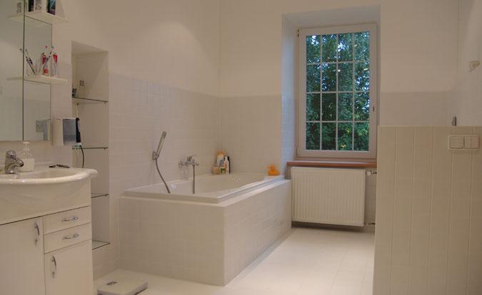 Prostorná koupelna v jednoduchém provedení je vybavena vanou