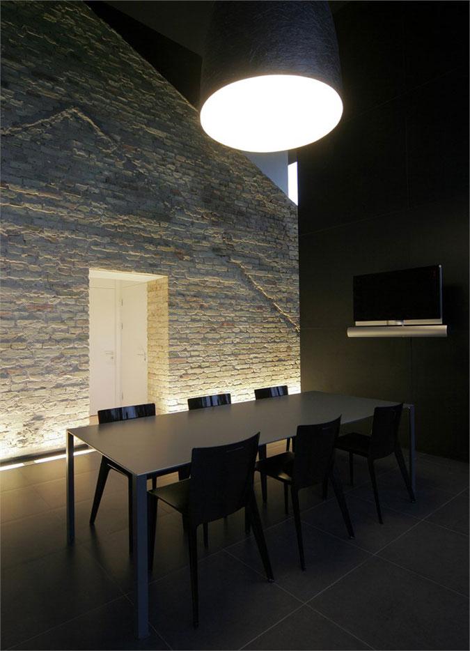 Rozsáhlé hladké plochy dlažby a skla v kontrastu s cihelnou strukturou.