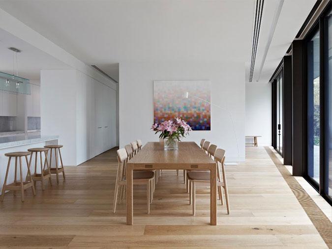Interiér využitívá bílých, pískovcových a dubových povrchů.