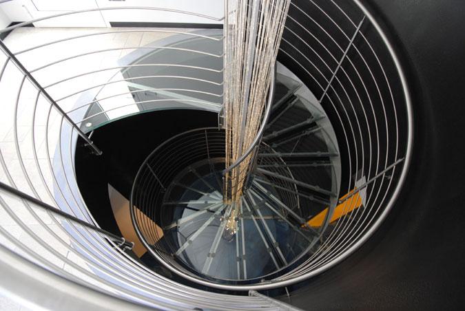 Vřetenové skleněné schodiště s nerezovými prvky.
